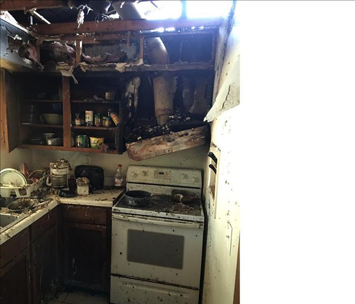 Kitchen area burnt, charred, opening in the roof