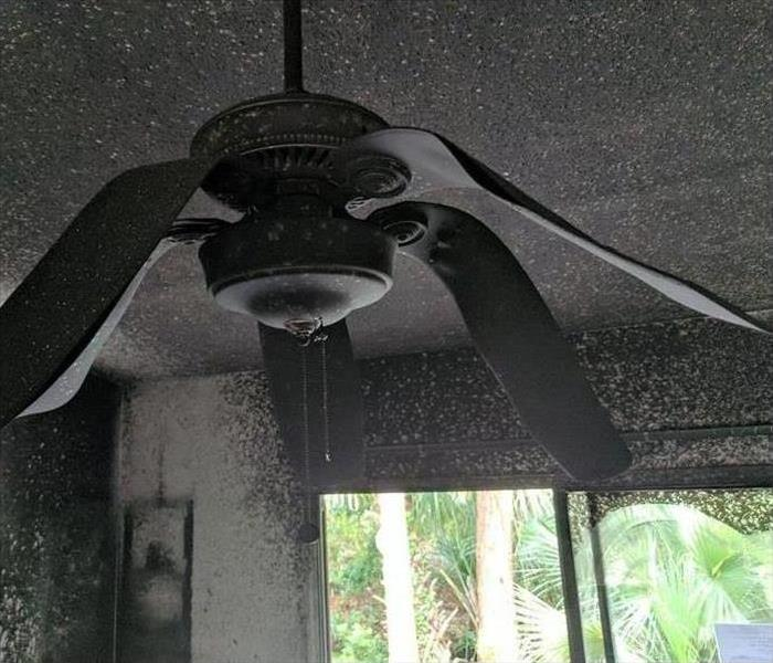 ceiling fan with melted and bent paddles from the heat of a fire in the room